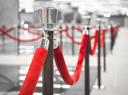 to queue: Red Carpet fence pole with red ropes Blurred interior background