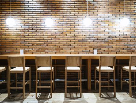의자와 조명 벽돌 벽 배경 소식통 로프트 인테리어와 테이블 카운터 바 스톡 콘텐츠