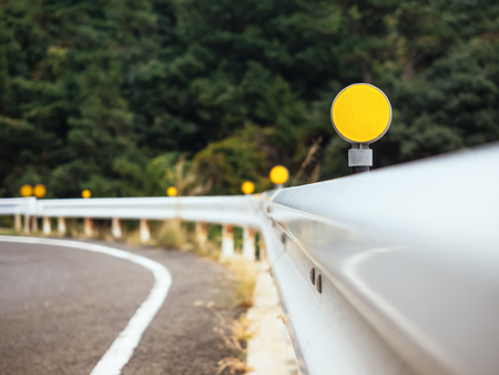 slow lane: Road curve Barrier with yellow Reflection Caution Sign on highway Stock Photo