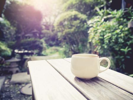 テーブル屋外庭背景朝日の出にコーヒー カップ 写真素材