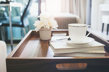 buen vivir: Interior de la casa con la taza de café libro flor blanca en la mesa de la bandeja de madera de estilo de vida inconformista fondo Foto de archivo