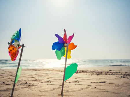 Pinwheel on sand Beach Summer holiday background outdoor with sunlight