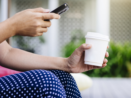 mocked: Hipster Hand holding Paper Cup coffee Outdoor Photo Sharing on Social Media Stock Photo