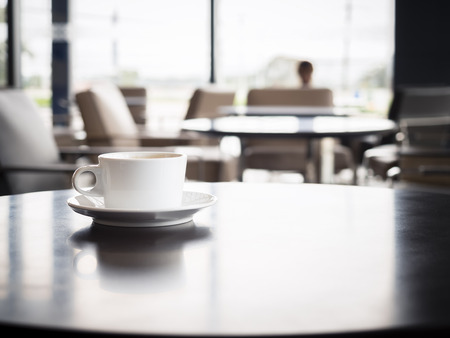 Coffee cup on table with blurred people in Restaurant shop cafe Interior seats Stock Photo