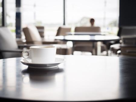 Taza de café en la mesa con la gente borrosa en la tienda de café de la tienda Asientos interiores