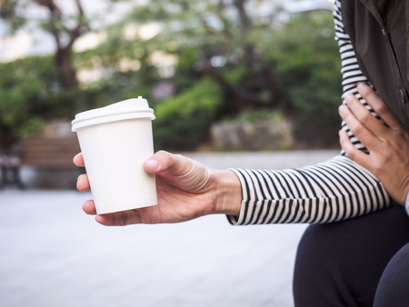 mocked: Woman Hipster Hand holding Paper Cup coffee Park Outdoor