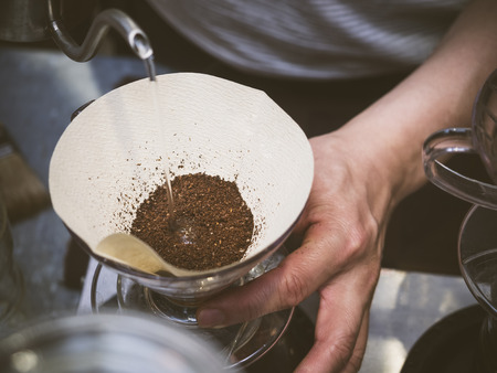 Hand drip coffee Barista pouring water on coffee ground with filter Foto de archivo