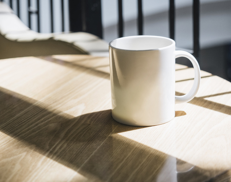 Mock up Coffee cup on table in cafe with sunlight
