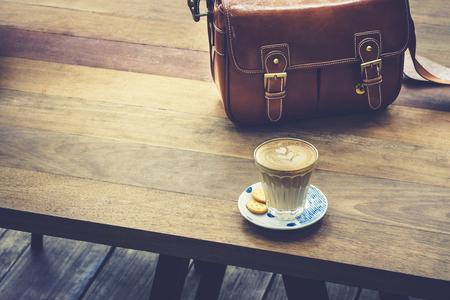 生活方式: 咖啡的木桌上用皮革包行家戶外生活方式