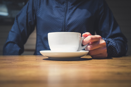 mocked: Hipster hand holding Coffee cup on table Cafe restaurant lifestyle Stock Photo