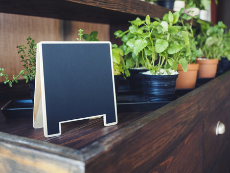 mocked: Mock up Menu Chalkboard stand with organic herb plants display on Wooden table