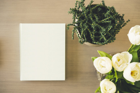 mocked: Blank Mock up Book cover on table with Plant white rose Flower