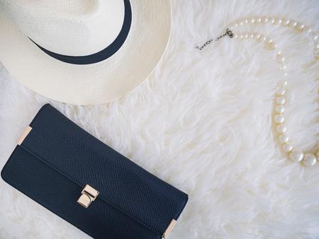 Sac d'embrayage de chapeau et un collier de perles sur fond de fourrure blanche concept beauté Girl Fashion