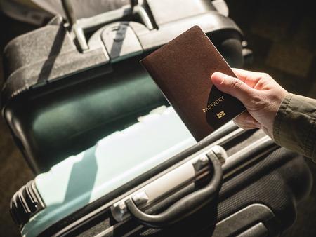 수하물 여행 개념을 가진 여권 여행자를 들고 손