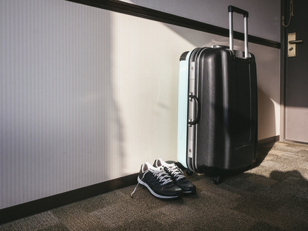 Travel Luggage with sport shoe in Hotel room Travel vacation concept