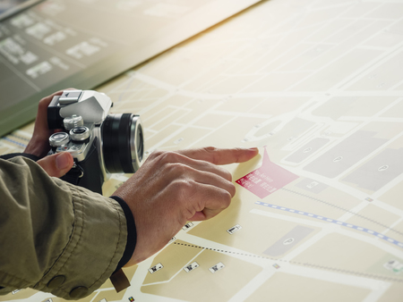 People hand point on map Tourist travel with camera