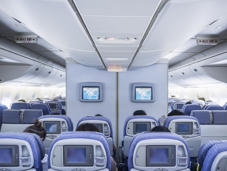 Airplane Interior flight on board with seat row and front screen monitor Stock Photo
