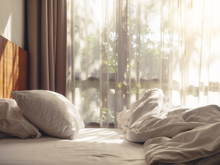 Bed Mattress and Pillows Mess up Bedroom in the morning with sunlight Archivio Fotografico