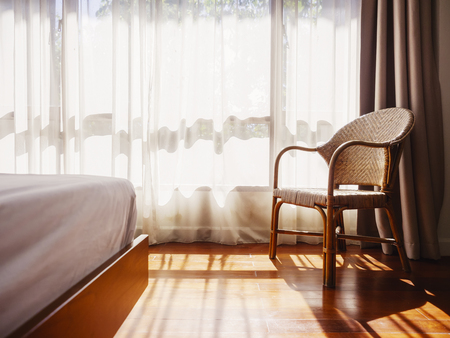 ラタンチェアベッドホワイトカーテン朝ライトホームデコレーション付きインテリアルーム木製フロア 写真素材