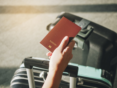 Hand holding Passport Traveler with Luggage Travel concept