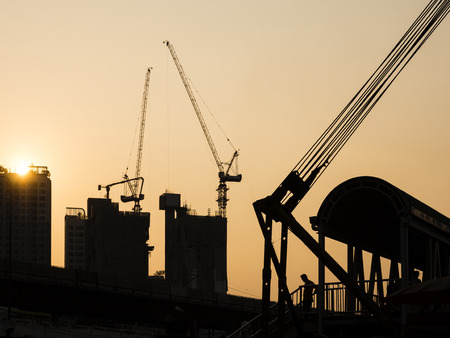 Cranes working on Building Construction site sunset sky Silhouette Industrial background 免版税图像 - 104425305
