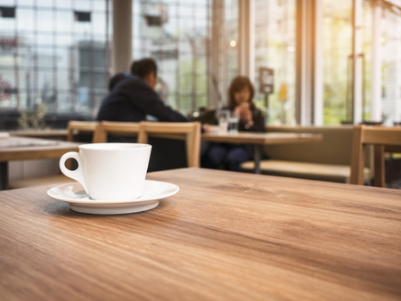 Coffee cup on table with Blur people Restaurant Cafe background
