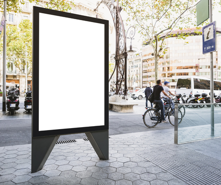 Mock up Banner stand Media outdoor Information Sign with people riding on City street Foto de archivo