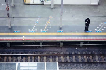 Man stand on train station platform Asian Business people using mobile phone Japan lifestyle in city