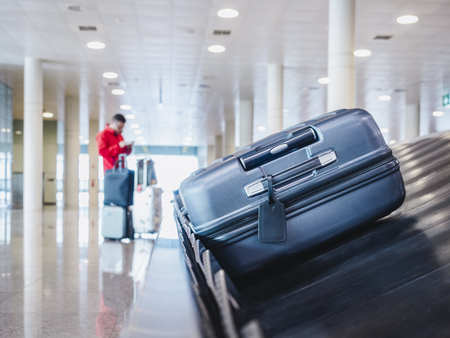 Suitcase or luggage on Baggage conveyor belt Airport Arrival hall People waiting