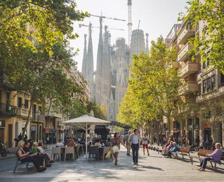 SPAIN, BARCELONA - OCT 21, 2018 : Cafe restaurant Cozy street in Barcelona city People walking Sagrada Familia Architecture landmark Sajtókép