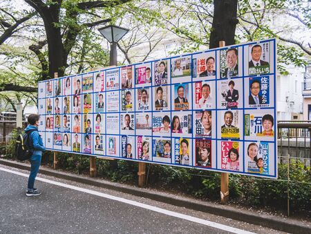 TOKYO, JAPAN - APR 17, 2019 : Japan local Election in Tokyo Candidate posters on board with Japanese people looking