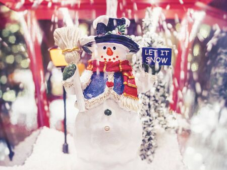 Snowman doll with Let it snow sign Snow falling Winter Xmas holiday festival decoration Stock Photo