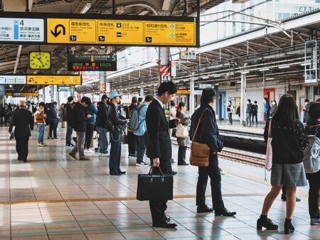 Businessman using mobile phone waiting Train on platform JR Train station Tokyo city Transportation. JAPAN, TOKYO - APR 14, 2019 Redactioneel