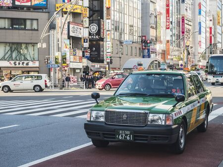 TOKYO, JAPAN - APR 18, 2018 : Taxi cab in Tokyo city Japan Asakusa district shopping area commercial sign Building 新聞圖片