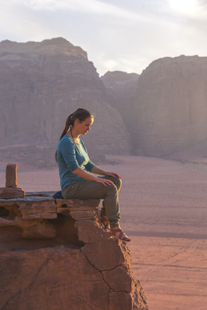the girl-traveler sits on a stone ledge against the backdrop of the mountains in the Wadi Wadi desert at sunset Stock Photo