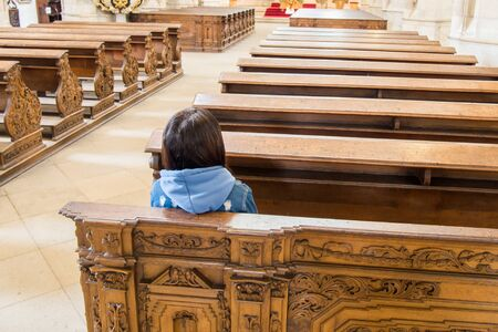 Young woman sitting in an empty church. Banque d'images