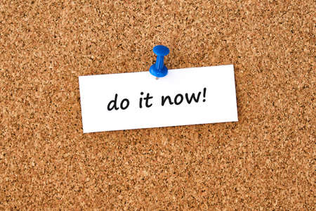 Do it now. Text written on a piece of paper or note, cork board background.