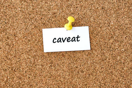 Caveat. Word written on a piece of paper, cork board background.