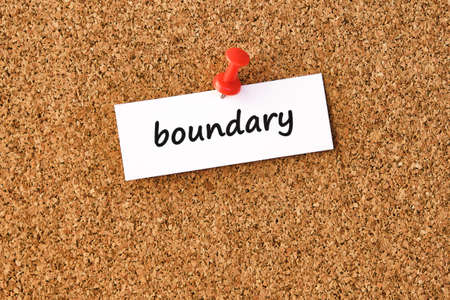 Boundary. Word written on a piece of paper, cork board background.