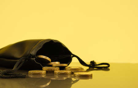 Coins falling out of a money pouch, golden background Archivio Fotografico