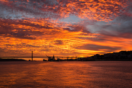 Incredible Golden sunset over the river Tagus, Bridge April 25 and the port Lisbon, Portugal.