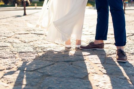 Newlyweds stand on stone pavement