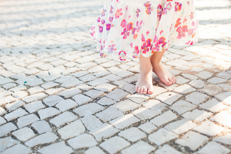 Little girl in dress stands on stone pavement
