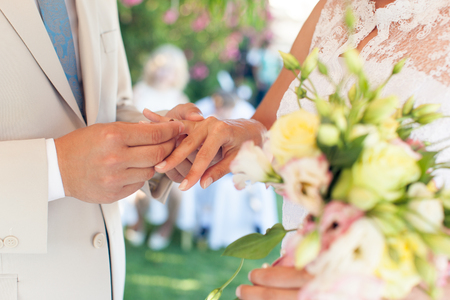 fingers put together: The groom wears a ring on the finger of the bride at a wedding Stock Photo
