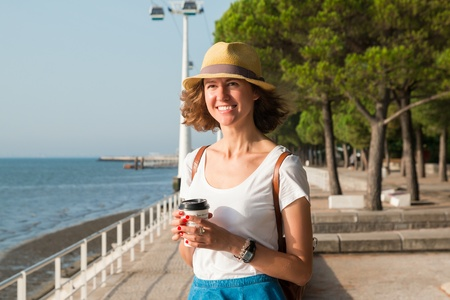 Attractive young woman walking in Lisbon near Tajus river at Park of the Nations