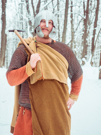 Medieval Irish warrior in mail and helmet holds a hammer in the winter forest