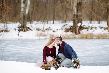 Stylish beautiful young couple bride and groom, dog sitting on the background of a winter landscape and river.