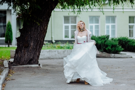 Street fashion concept: portrait of young beautiful woman wearing wedding white dress and pink coat in the city. Redhair girl outdoor. Old architecture background. Amazing tattoo bride. Color. Stock Photo