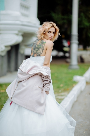 Street fashion concept: portrait of young beautiful woman wearing wedding white dress and pink coat in the city. Redhair girl showing spin outdoor. Old architecture background. Amazing tattoo bride.