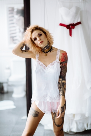 Closeup portrait tattoo red hair girl. Fashion concept: portrait of young beautiful woman wearing lingerie in bedroom of apartaments hotel.